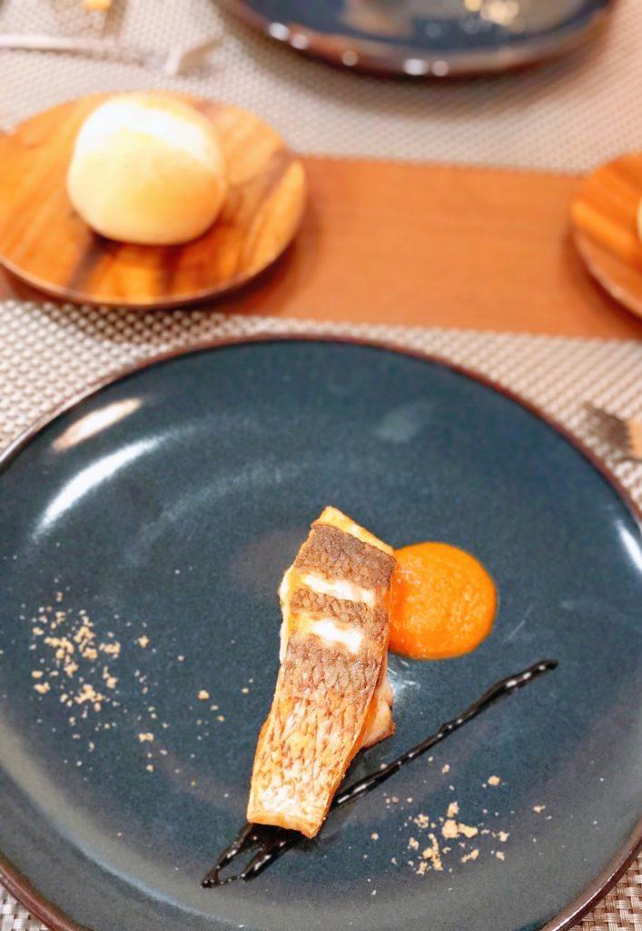 お魚料理とパンの画像